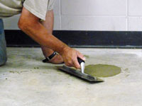Repairing the cored holes in the concrete slab floor with fresh concrete and cleaning up the Frankfort home.