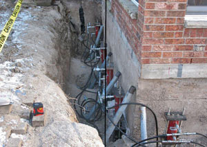 Foundation push piers installed around a house with a foundation settlement issues in Campbellsville