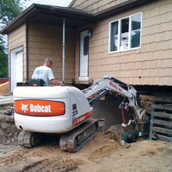 Excavating to expose the foundation walls and footings for a replacement job in Independence