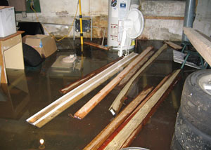 A severely flooding basement in Elizabethtown, with lumber and personal items floating in a foot of water