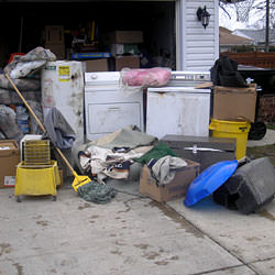 Soaked, wet personal items sitting in a driveway, including a washer and dryer in Florence.