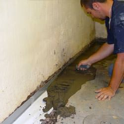 A basement waterproofer installing a perimeter drain system in Shelbyville